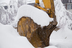 Excavator shovel covered with snow. Close-up image of excavator shovel covered with snow Royalty Free Stock Photo