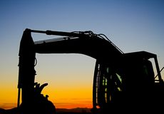 Excavator silhouette. Excavator parked with a sunset background Stock Photo