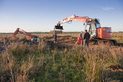 Excavator sinks. Rescue workers try to recover tracked excavator lost in peat on the somerset levels and moors Royalty Free Stock Image