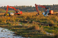Excavator sinks. Recovery teams continue working into the evening to recover tracked excavator lost in peat on the somerset levels and moors Royalty Free Stock Photo