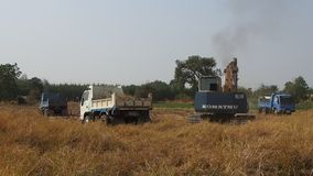 Excavator and small trucks on agricultural land stock footage