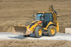 Excavator standing on a road under construction Royalty Free Stock Images