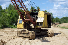 Excavator standing on sand near forest on summer day Royalty Free Stock Photography