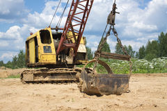 Excavator standing on sand near forest on summer day Royalty Free Stock Photo