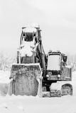 Excavator standing in the snow outdoors in winter, close up Royalty Free Stock Photo