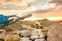 Excavator and stone crusher in a quarry royalty free stock photography