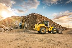 Excavator and stone crusher in a quarry stock image