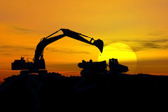 Excavator in storm. Stock image of earth mover trying to get a last load before the storm Royalty Free Stock Images