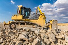 Excavator surrounded by granite rock to transform into gravel stock image