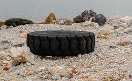 Excavator tire on the seashore Royalty Free Stock Photos