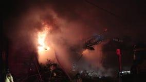 Excavator to demolishing intense burning home. Excavator to demolishing burning home.Blaizing building stock video footage