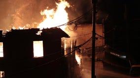 Excavator to demolishing intense burning home. Excavator to demolishing burning home. Blazing building stock footage