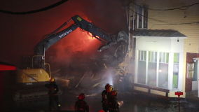 Excavator to demolishing intense burning home. Firefighters spray water on background stock video footage