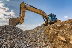 Excavator on top of a mountain of stone and sand from a quarry royalty free stock photo