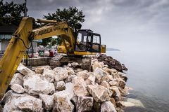 Excavator On Top Of Rocks By The Sea - Turkey stock photo