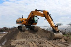 Excavator on top of sand pile. Excavator standing on top of sand pile waiting for truck with greenhouse, houses, river and cloudy blue sky in background Royalty Free Stock Photography