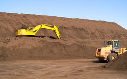 Excavator on Top Soil hill. A construction loader and an excavator on a hill of top soil Royalty Free Stock Photography