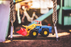 Excavator toy on a swing. A children's excavator toy, placed on a swing at a playground Stock Image