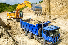 Excavator and truck in the road construction job, countryside of Myanmar Stock Images