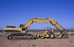 Excavator and tractor. Heavy equipment excavator with gannon tractor parked under arm Royalty Free Stock Images