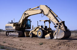 Excavator and tractor. Heavy equipment excavator with gannon tractor parked under arm royalty free stock photos