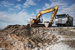 Excavator and truck on a construction site Royalty Free Stock Image
