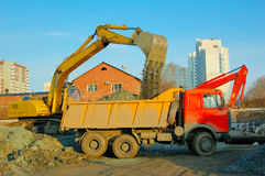Excavator and truck move earth. At building site Stock Image
