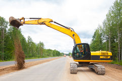 Excavator unloading soil during road construction Royalty Free Stock Photography