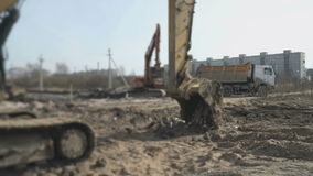 Excavator uploads a clay in a truck using a bucket. Excavator uploads a clay in a truck using a excavator bucket at construction site. Working process stock video