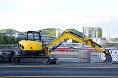 Excavator used for the reconstruction of the roadway in the city royalty free stock photo