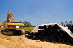 Excavator and water pipes. A view of a large, heavy duty construction shovel and a pile of large water main pipes to be laid underground on a construction site Royalty Free Stock Photography