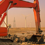 Excavator and Windmills. Windmills framed by the arm of an excavator Stock Image