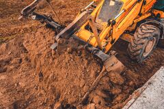 Free Excavator With A Large Iron Bucket On A Construction Site During Road Works, Backhoe Dig The Ground For The Foundation Royalty Free Stock Photo - 176626365