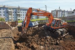 Excavator woking on constraction site. Divnogorsk, Russia - June 16: Construction of a house, preparation of a trench with the technics in Divnogorsk, Russia on Stock Images
