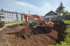 Excavator woking on constraction site. Divnogorsk, Russia - June 16: Construction of a house, preparation of a trench with the technics in Divnogorsk, Russia on Royalty Free Stock Image