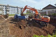 Excavator woking on constraction site. Divnogorsk, Russia - June 16: Construction of a house, preparation of a trench with the technics in Divnogorsk, Russia on Stock Photos