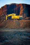 Excavator on a woodchips pile stock photography