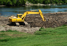Excavator At Work. A view from above as an excavator digs an move earth around below under a bright sun in Dayton, Ohio Stock Image