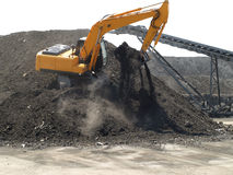 Excavator at work. Excavator scooping dirt on transport belt Royalty Free Stock Image