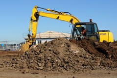 Excavator At Work. Yellow excavator on a construction site Stock Photography