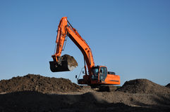 Excavator at work. Orange excavator at work in open sand mine and a blue sky Stock Photos