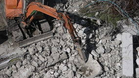 Excavator at work destroying a concrete wall stock footage