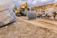 Excavator in a work extracting granite to transform into gravel.  stock image