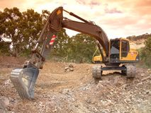 Excavator at work. Moving and digging dirt with soil earth works construction in new housing development subdivision. Earth mover bucket excavation landscaping Stock Photo