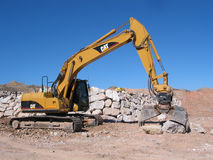 Excavator at Work. A trackhoe tractor stacks a rock wall in southern Utah Royalty Free Stock Photo