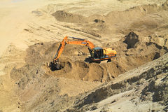 Excavator working on the bottom of the quarry on a sunny day. POLEWOJE, KALININGRAD REGION, RUSSIA — JUNE 18, 2014: Excavator working on the bottom of the Royalty Free Stock Images