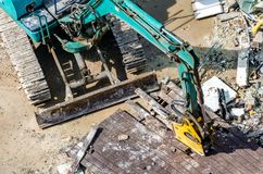 An excavator working at demolition site. An excavator working at demolition building site in Bnagkok, Thailand Royalty Free Stock Image