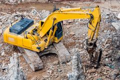 An excavator working at demolition site. An excavator working at demolition building site in Bnagkok, Thailand Stock Photo