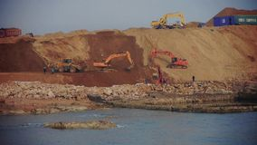 Excavator working & dumper truck on construction site near sea. Excavator working & dumper truck on construction site near sea.  gh2_06108 stock video footage