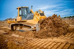 Excavator working with earth and sand in sandpit Stock Images